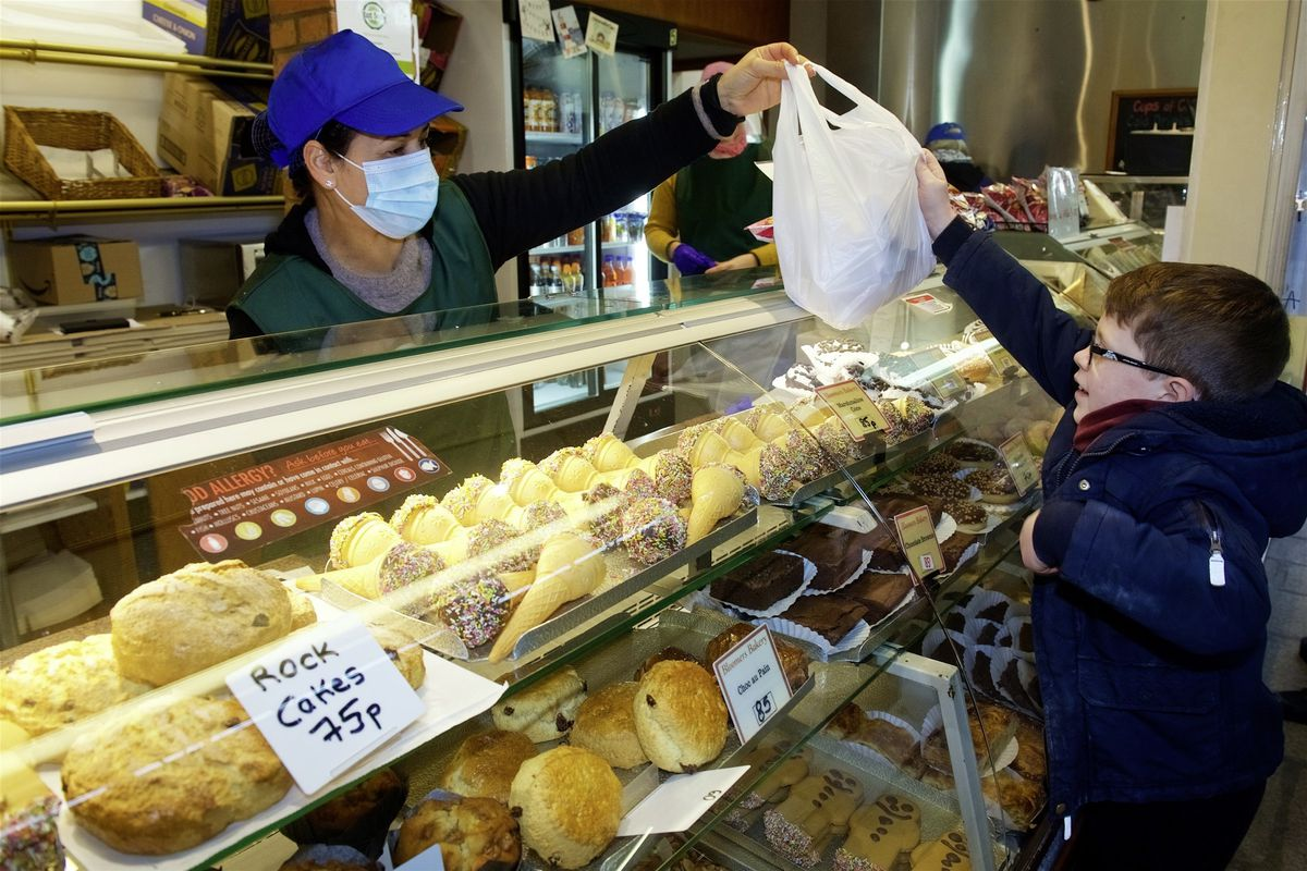 Most of the shops in Jersey's Central Market are open under its Covid-19 restrictions, including Bloomers Bakery with staff member Vania Faria handing Harris Stephens, 6, his two chicken and sweetcorn sandwiches, a Corn Flake cake and a gingerbread man. (Picture by Rob Currie, 29090271)